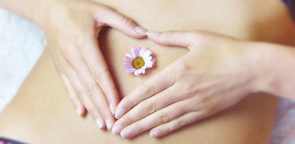 Mulher com as mãos ao centro da barriga com uma pequena flor ao centro